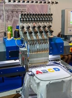 Letras coloridas de bordado de máquina de costura profissional. tecido, ninguém. produção de fábrica, fabricação de costura, tecnologia de costura