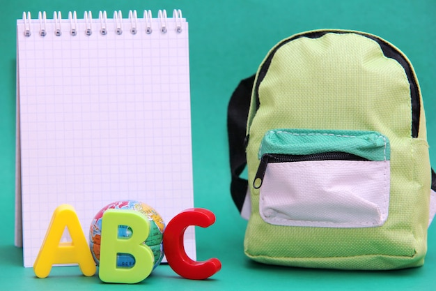 Letras coloridas do alfabeto inglês ao lado de um globo de brinquedo e um bloco de notas. o saco da escola.