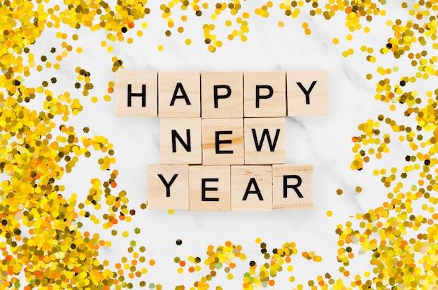 Letras de ano novo, cercadas por glitter dourado
