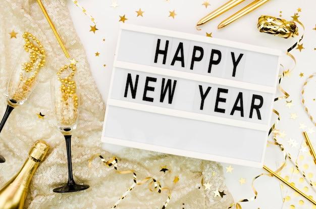 Letras de ano novo com garrafa e copos de champanhe