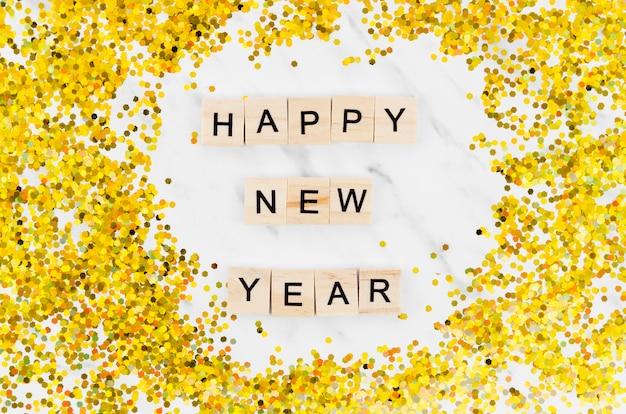 Letras de ano novo em fundo de mármore e glitter dourado