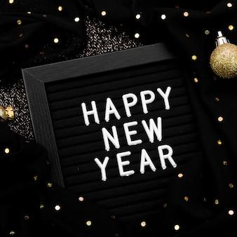 Letras de ano novo em fundo escuro com luzes