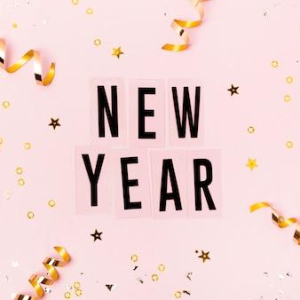 Letras de ano novo em fundo rosa com fitas douradas