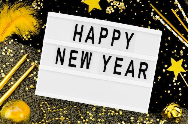 Letras de ano novo em um cartão branco com acessórios de ouro