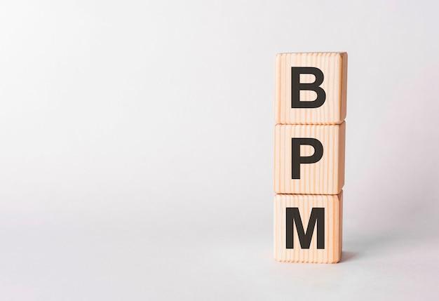 Letras de bpm de blocos de madeira em forma de pilar no fundo branco, copie o espaço