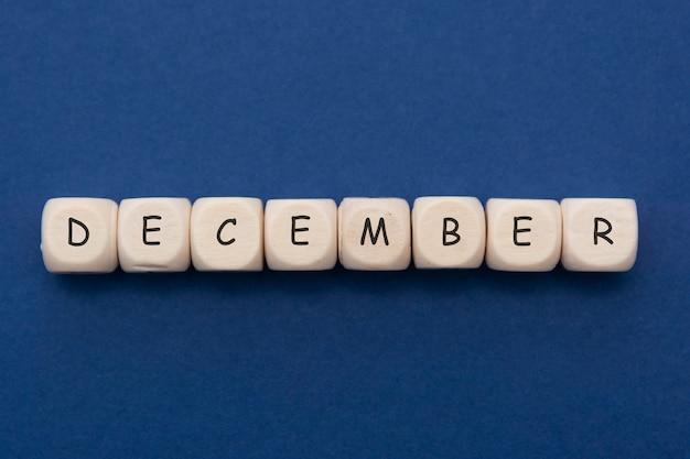 Letras de dezembro, blocos de madeira com palavra de dezembro sobre azul clássico