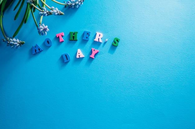 Letras de dia das mães com flores azuis da primavera