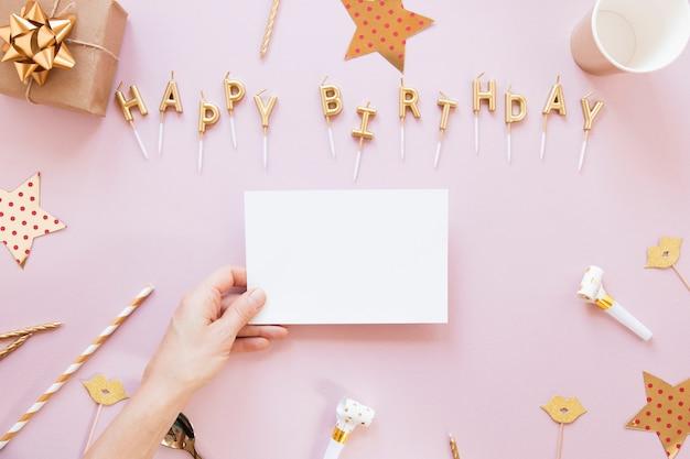 Letras de feliz aniversário em fundo rosa com cartão vazio