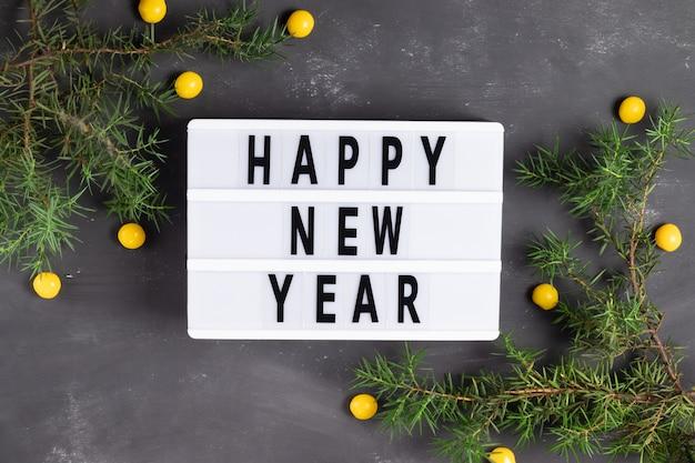 Letras de feliz ano novo no quadro de giz cinza com galhos de pinheiro 2021