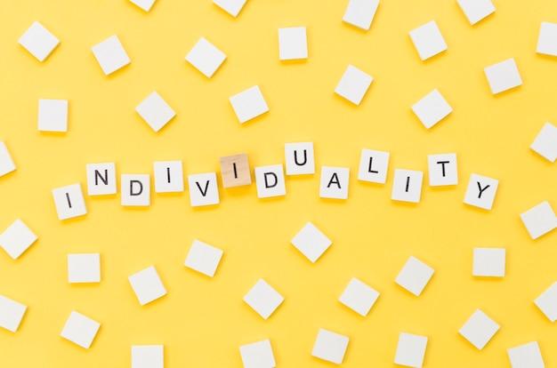 Letras de individualidade feitas com cubos de madeira em fundo amarelo