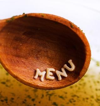 Letras de macarrão com palavra de menu na colher de pau