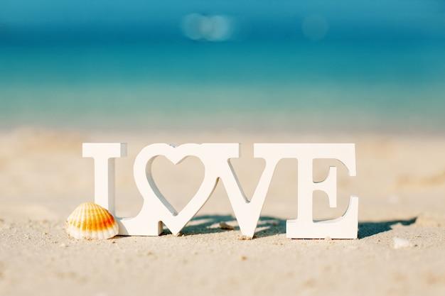 Letras de madeira amor em uma praia com vista para o mar azul