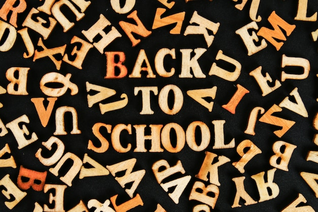 Letras de madeira com texto no centro de volta à escola num quadro-negro. o conceito de ler
