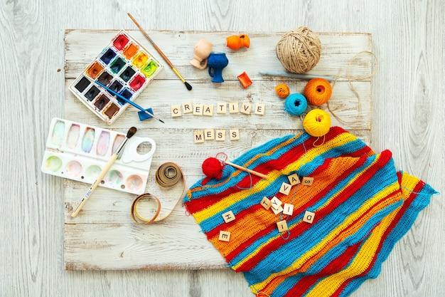 Letras de madeira com tricô e materiais de desenho, bagunça criativa. fique em casa, esteja seguro.