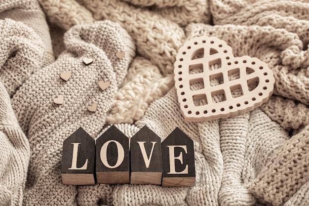 Letras de madeira compõem a palavra amor em um fundo de itens de malha aconchegantes. conceito de feriado do dia dos namorados.