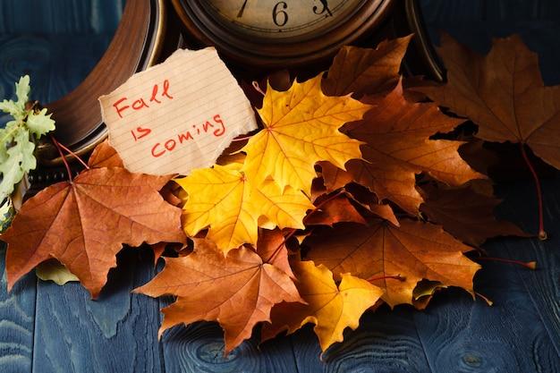 Letras de madeira de ação de graças feliz com uma abóbora de outono e borda de canto de folhas contra madeira velha