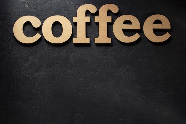 Letras de madeira de café na superfície preta