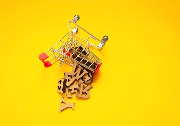 Letras de madeira espalhadas do alfabeto inglês de um carrinho de compras em miniatura em um fundo amarelo, close-up. conceito de redação e educação. copie o espaço.