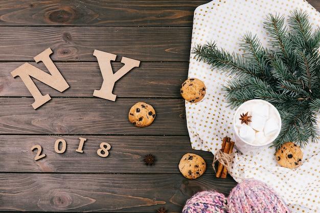 Letras de madeira 'ny 2018' encontram-se no chão cercado de biscoitos, ramos de abeto e meias quentes