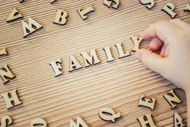 Letras de madeira, palavras. foco seletivo. mãos de criança.
