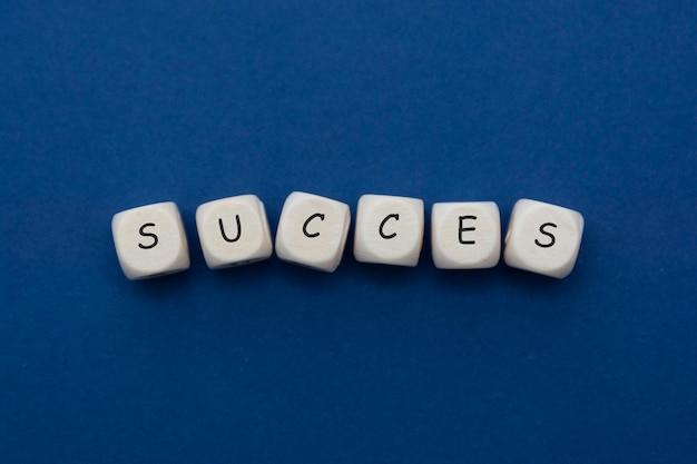 Letras de palavra sucesso, cubos de madeira, isolados em azul, azul clássico.