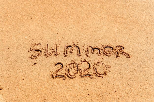 Letras de verão 2020 na praia com ondas e mar azul claro. viajar nas férias de verão