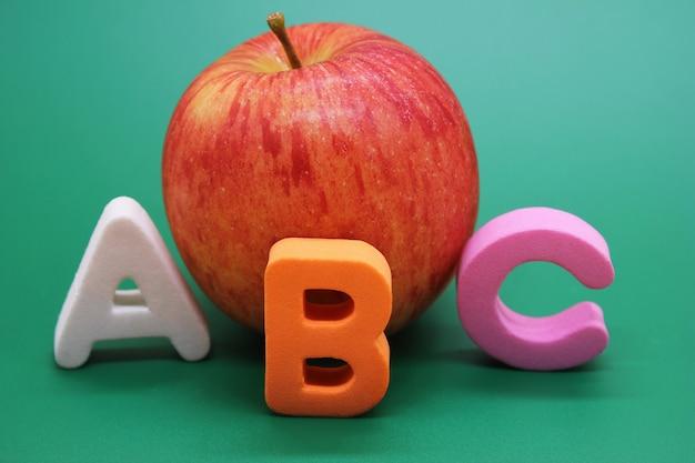 Letras do alfabeto inglês abc ao lado de livro e apple.