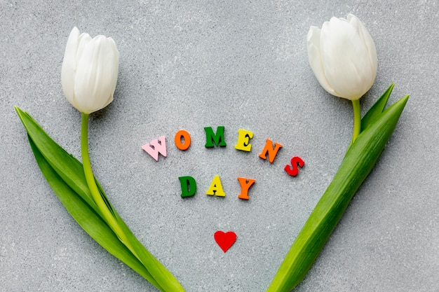 Letras do dia da mulher em cimento com tulipas brancas