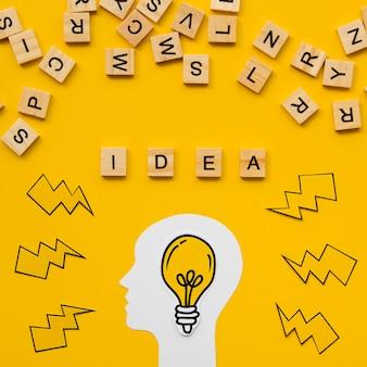 Letras do scrabble e palavra do conceito da ideia com lâmpada