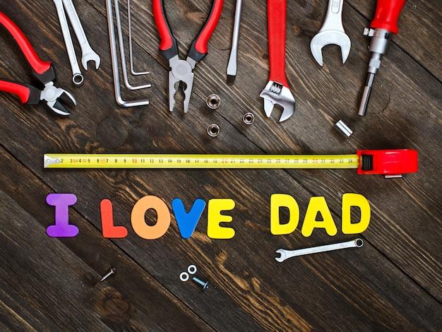 Letras e ferramentas em um dia de pai de fundo de madeira