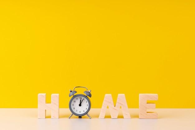 Letras em casa com letras de madeira e relógio em fundo amarelo