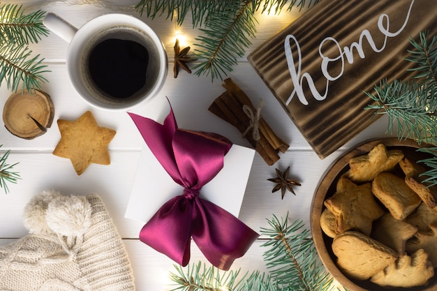 Letras em casa sinal de madeira queimada biscoito de pão de gengibre galhos de árvore de natal xícara de café presente em paus de canela na superfície branca camada plana