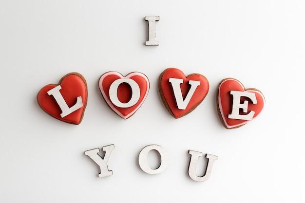 Letras eu te amo e corações de gengibre festivos no dia dos namorados em fundo branco