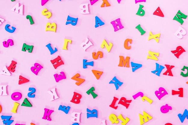 Letras multicoloridas do alfabeto inglês em um fundo rosa, fundo de letras. conceito de educação.