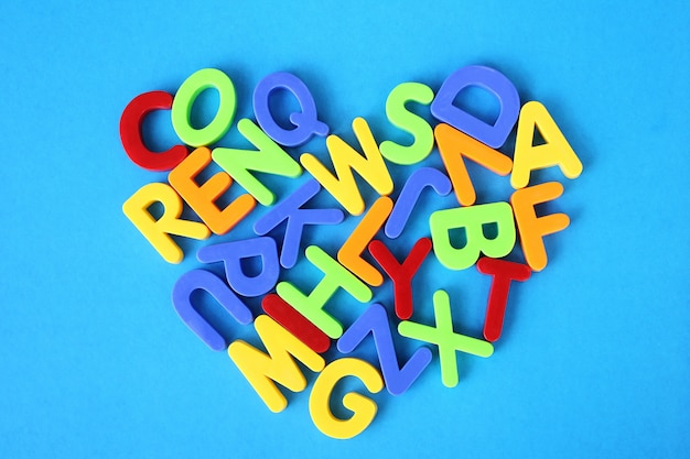 Letras multicoloridas do alfabeto inglês são colocadas em forma de um coração em um fundo azul.