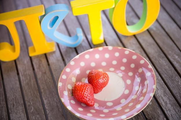 Letras russas coloridas palavra verão e prato com morangos na mesa de madeira ao ar livre