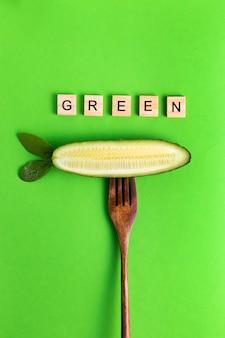 Letras vegan vegan saudável eco pepino em um garfo de madeira sobre uma superfície verde