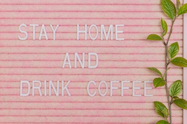 Lettreing booard com citação fica em casa e bebe café decorado com galho de primavera com folhas verdes frescas. fundo de motivação de primavera