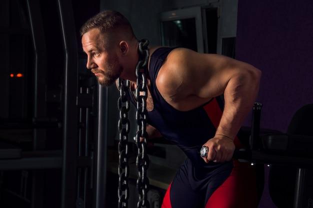 Levantador de peso com uma enorme corrente de metal em volta do pescoço. flexões nas barras irregulares do ginásio