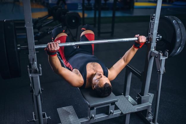 Levantador de peso em máquina de exercício com barra