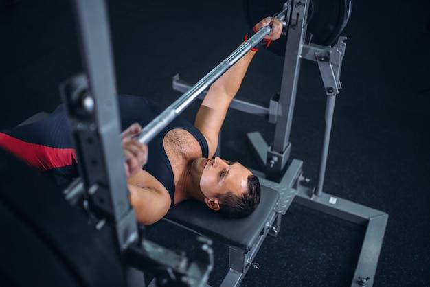 Levantador de peso forte em roupas esportivas na máquina de exercícios com barra, vista superior