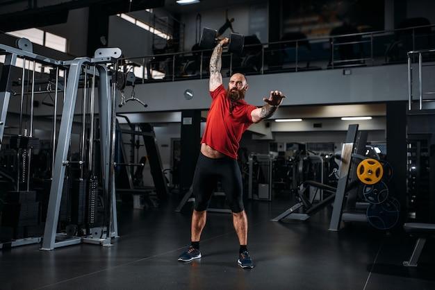 Levantador de peso forte fazendo exercícios com halteres, treino no ginásio.