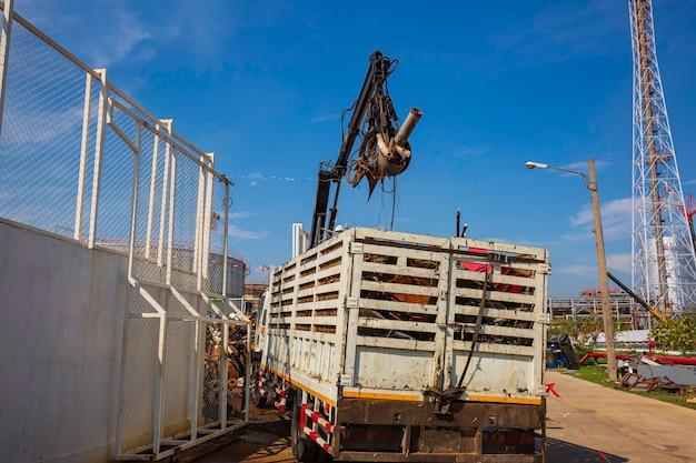 Levantadores de sucata do trabalhador no braço de manuseio hidráulico, caminhão, tubulação, óleo e gás