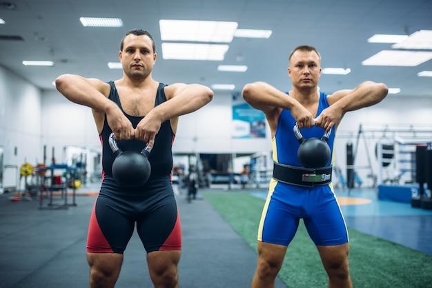 Levantadores masculinos fortes fazendo exercícios com kettlebell, levantando treinamento no ginásio.