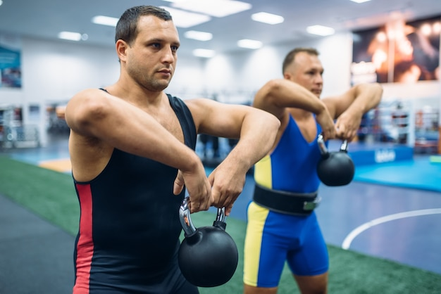 Levantadores masculinos fortes fazendo exercícios com kettlebell