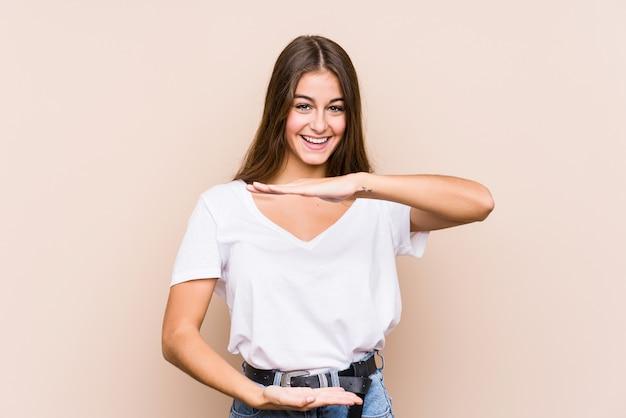 Levantamento caucasiano novo da mulher isolado guardando algo com ambas as mãos, apresentação do produto.