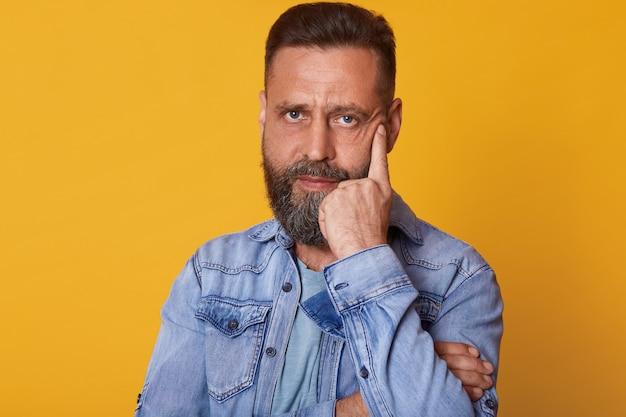 Levantamento de olhos azuis magnético sério interior posando isolado sobre parede amarela brilhante, vestindo jaqueta jeans casual