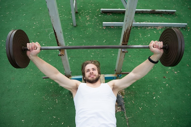 Levantamento de peso, musculação, fitness, esporte. fisiculturista levanta a barra no estádio. homem com torso atlético, braços fortes, treinando com peso. potência, energia, conceito de força