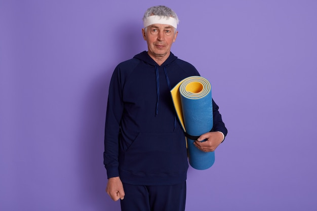 Levantamento interno do homem maduro isolado no lilás com tapete de ioga nas mãos, terno de esportes vestindo masculino e faixa principal, poses sênior do indivíduo após o treinamento desportivo. aptidão, conceito ativo de velhice.