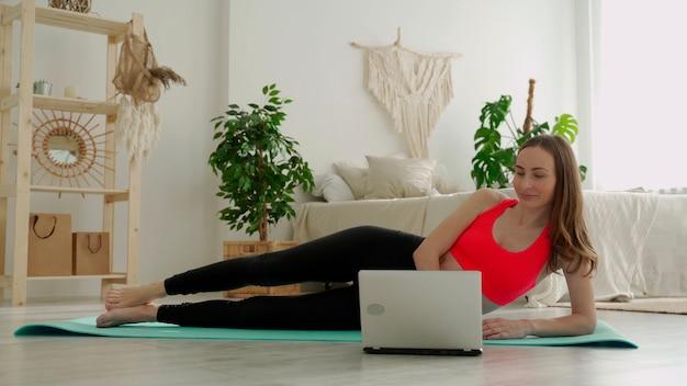 Levantando a perna da posição deitada de uma jovem que está fazendo seus exercícios em casa usando um laptop